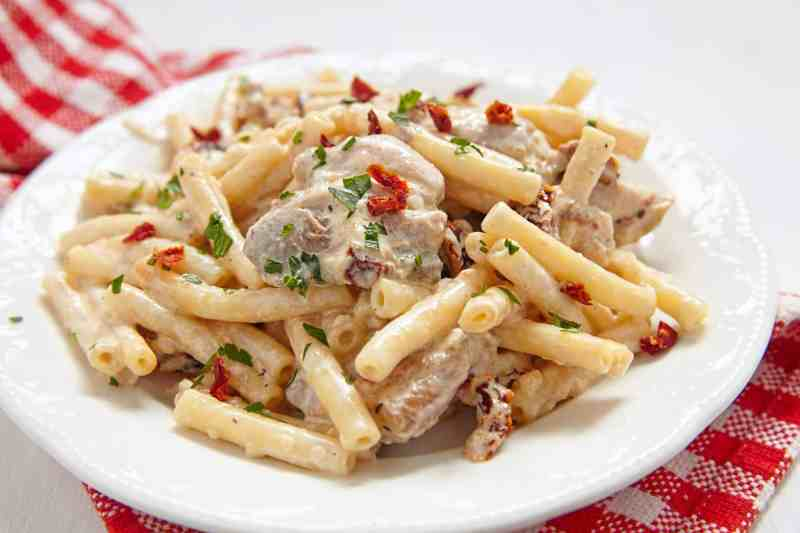 Crock Pot Creamy Italian Chicken Pasta on a white plate with a red napkin