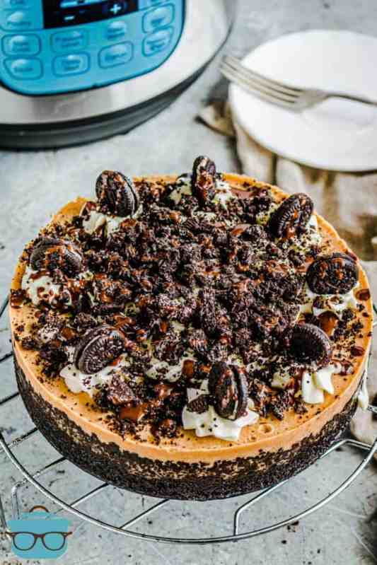 Instant Pot Oreo Pumpkin Cheesecake, fully baked and decorated on top of a cooling rack