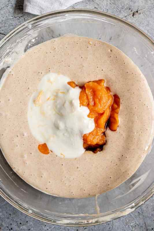 pumpkin, sour cream and vanilla extract added to pumpkin spice cream cheese mixture in a clear bowl