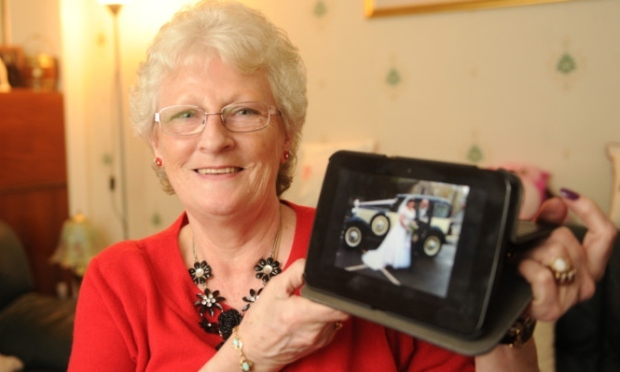 Moyra with a picture of her son's wedding. She praised Ballumbie Court care home staff after they arranged for her mother to view the happy day on Skype.