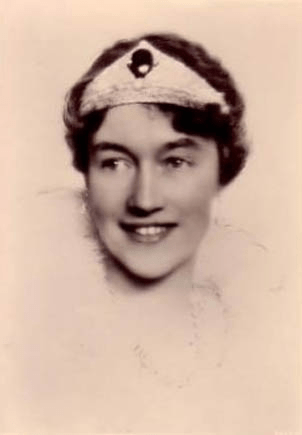 Charlotte wears the Chaumet Emerald Tiara, supplemented by either additional jewels or fabric, across her forehead in this portrait, ca. 1921
