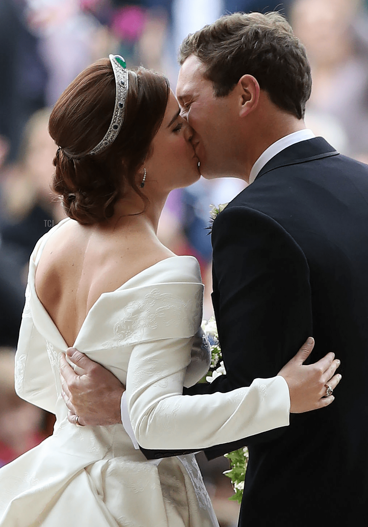 Britain's Princess Eugenie of York (L) and her husband Jack Brooksbank kiss as they emerge from the West Door of St George's Chapel, Windsor Castle, in Windsor, on October 12, 2018 after their wedding ceremony