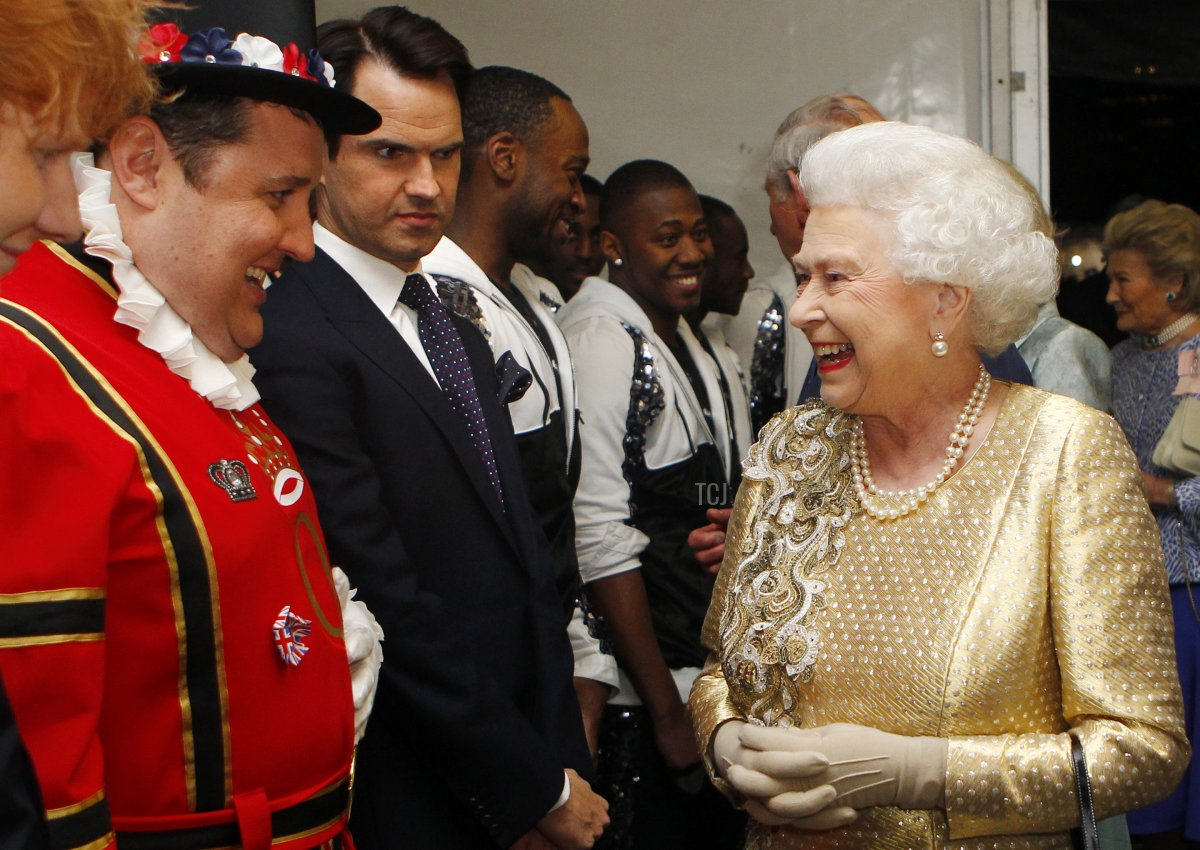 Queen Elizabeth II greets Peter Kay (L) and Jimmy Carr (2ndL) backstage during the Diamond Jubilee Concert outside Buckingham Palace in London, on June 4, 20112. A chain of more than 4,200 beacons began to flare across the globe Monday to mark Queen Elizabeth II's diamond jubilee, with the last to be lit by the monarch at a star-studded concert at Buckingham Palace