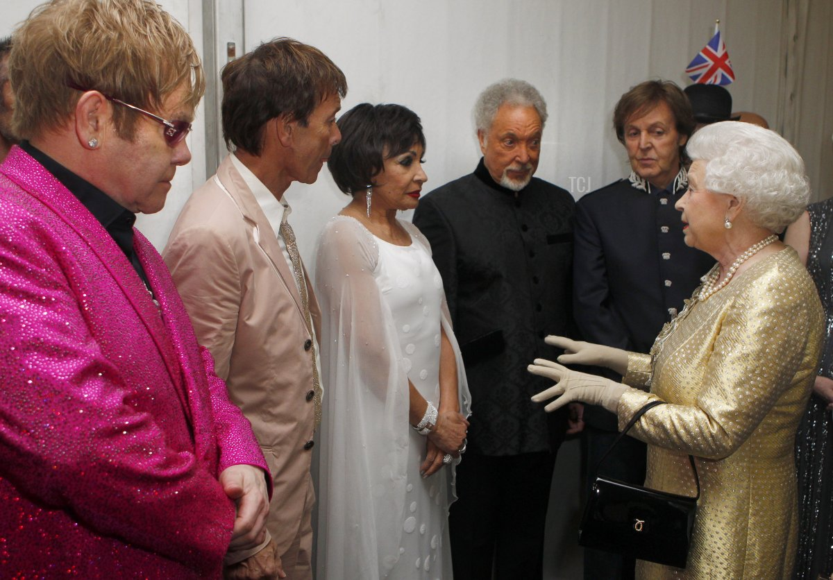 Queen Elizabeth II greets (L-R) Sir Elton John, Sir Cliff Richard, Dame Shirley Bassey, Sir Tom Jones and Sir Paul McCartney backstage as British singer Sir Elton John (L) watches during the Diamond Jubilee Concert outside Buckingham Palace in London, on June 4, 20112. A chain of more than 4,200 beacons began to flare across the globe Monday to mark Queen Elizabeth II's diamond jubilee, with the last to be lit by the monarch at a star-studded concert at Buckingham Palace