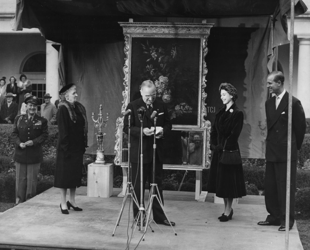 Princess Elizabeth and Prince Philip, the Duke of Edinburgh, smiling as President Harry Truman gives a speech and his aide, General Harry Vaughan (extreme left) looks on, in Washington DC, November 5th 1951