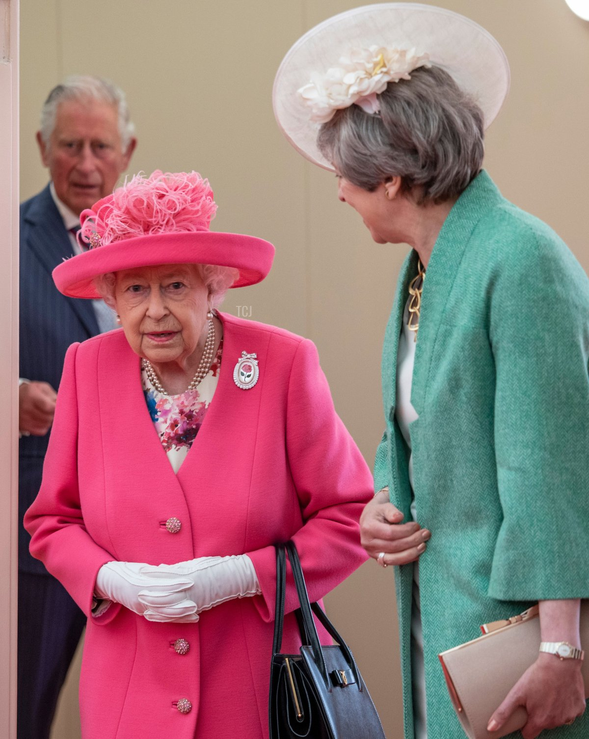 Britain's Queen Elizabeth II (C) talks with Britain's Prime Minister Theresa May (R) followed by Britain's Prince Charles, Prince of Wales (L) as they attend an event to commemorate the 75th anniversary of the D-Day landings, in Portsmouth, southern England, on June 5, 2019