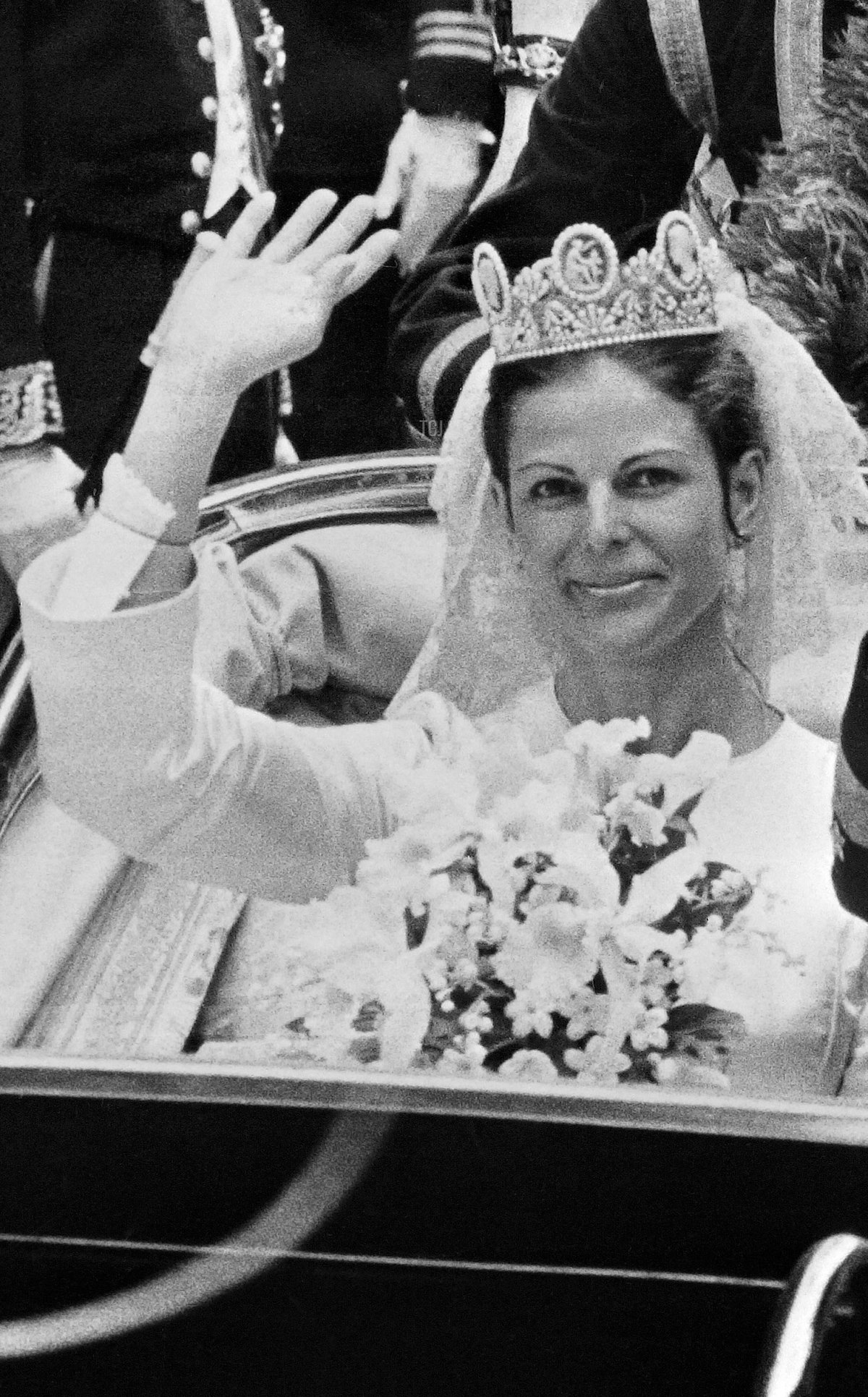 King Carl XVI Gustaf of Sweden and Miss Silvia Sommerlath are seen waving to the crowd from their coach during their wedding ceremony in Stockholm on June 19, 1976
