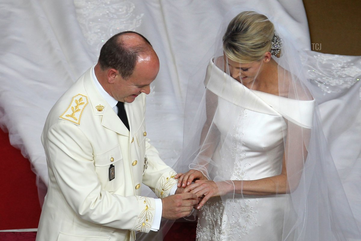Prince Albert II of Monaco puts the ring on the finger of the left hand of Princess Charlene of Monaco at the altar during their religious wedding at the Main Courtyard of the Prince's Palace on July 2, 2011 in Monaco