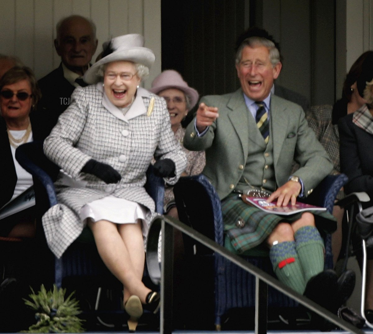 Queen Elizabeth II and Prince Charles, The Prince of Wales laugh as they watch competitors during the Braemar Gathering at the Princess Royal and Duke of Fife Memorial Park on September 2, 2006 in Braemar, Scotland