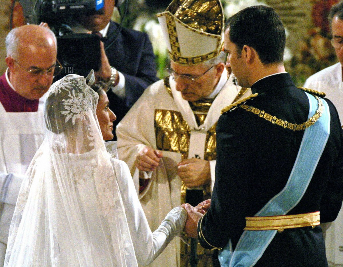 Spanish Crown Prince Felipe of Bourbon puts the ring onto the finger of his bride Letizia Ortiz in front of Madrid's Archbishop Antonio Maria Rouco Varela (C) during their wedding ceremony at Almudena Cathedral in Madrid 22 May 2004