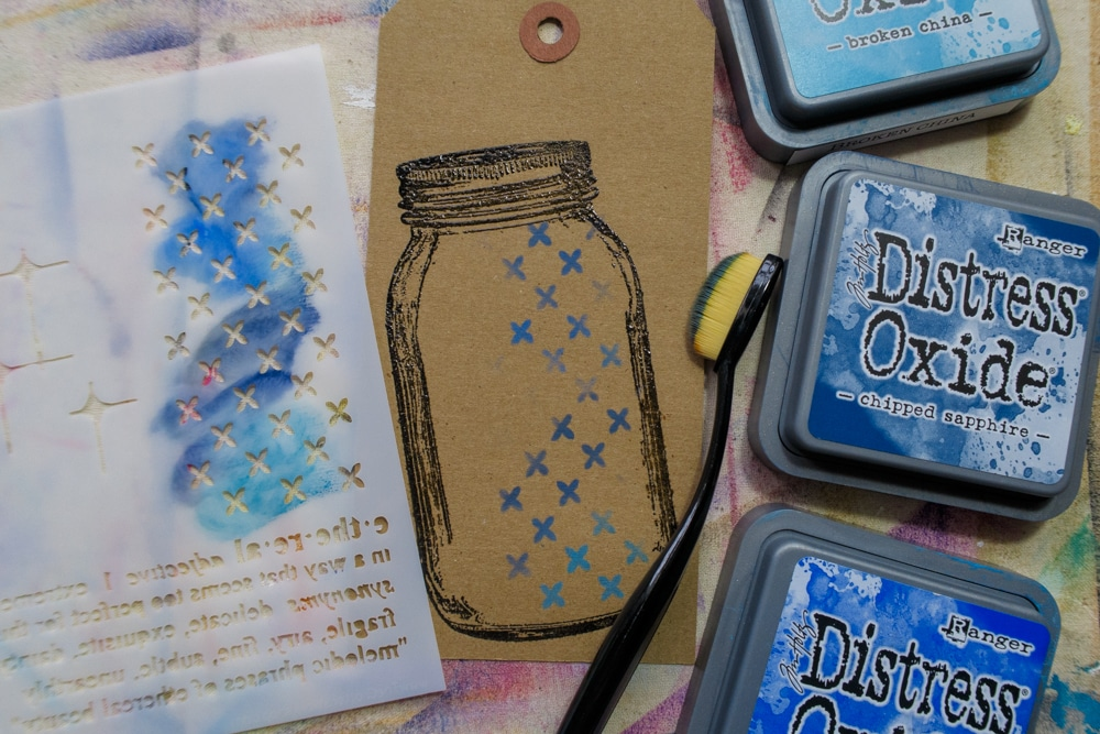 Adding stencilling to stamped image using Distress inks in shades of blue