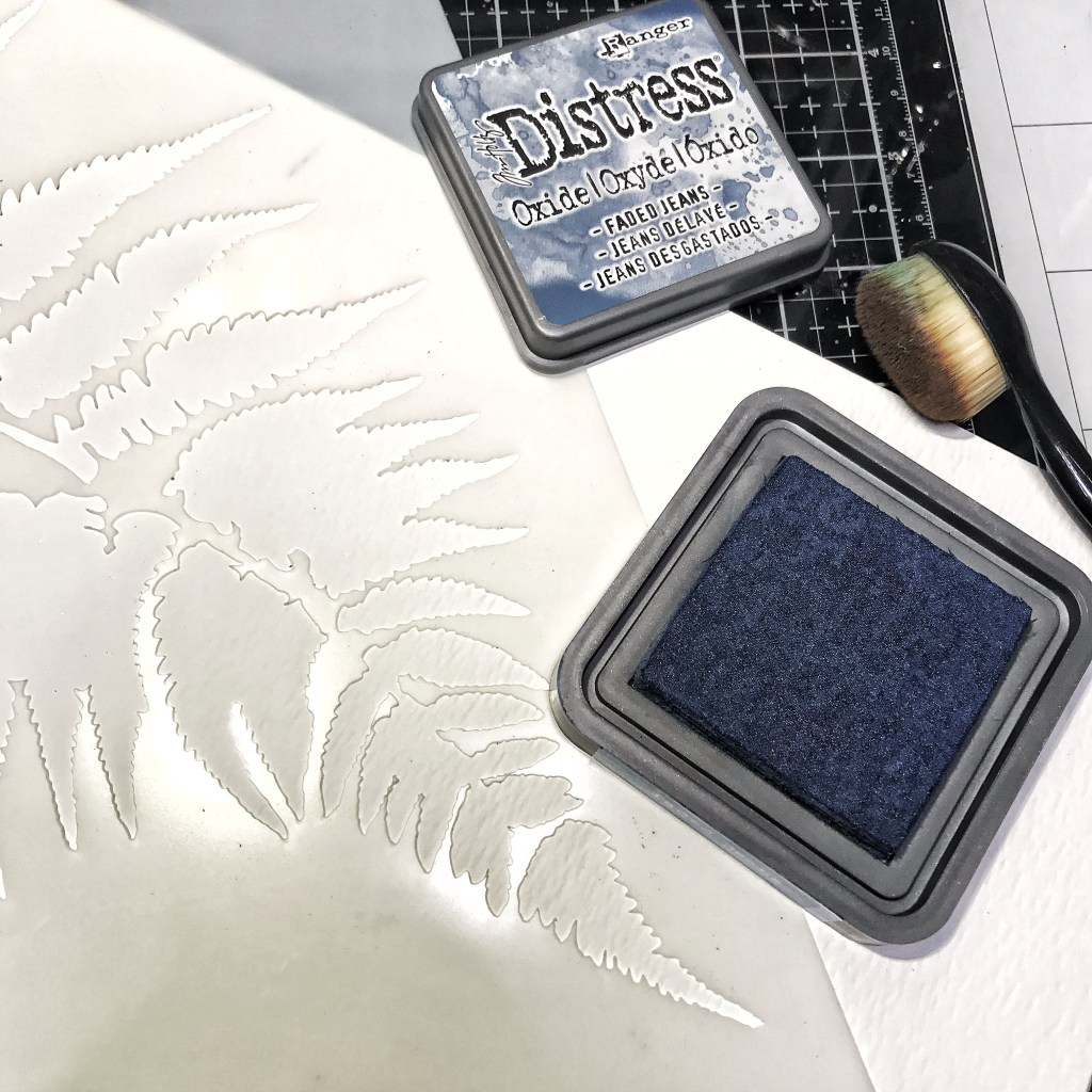 Ranger Tim Holtz Distress Oxide Ink Pad in Faded Jeans through TCW243 Ferns Stencil onto TCW9051 Watercolor Paper with blending brush
