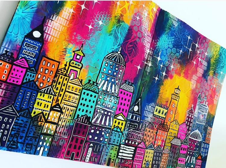 art journal page with a city scene. Lots of buildings with black outline over a rainbow patterned background. Tammy Klingner #tcwstencillove