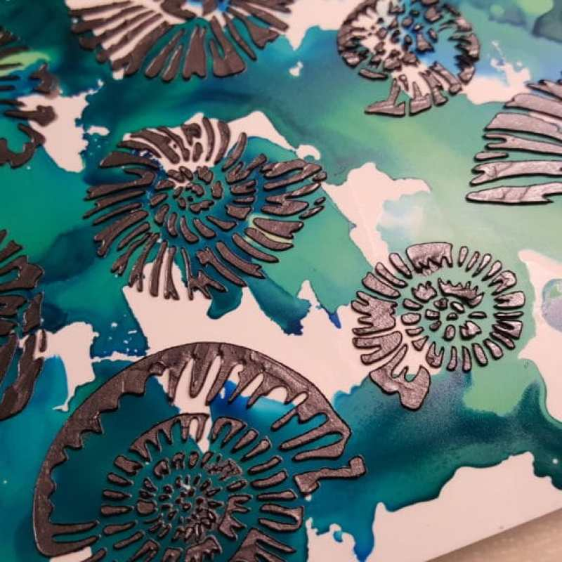 Marcasite silver modeling paste applied with a palette knife through the TCW500 Nautilus stencil on top of blue and green alcohol inks on yupo paper.