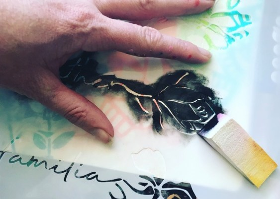 applying black paint with a sponge through a floral word stencil