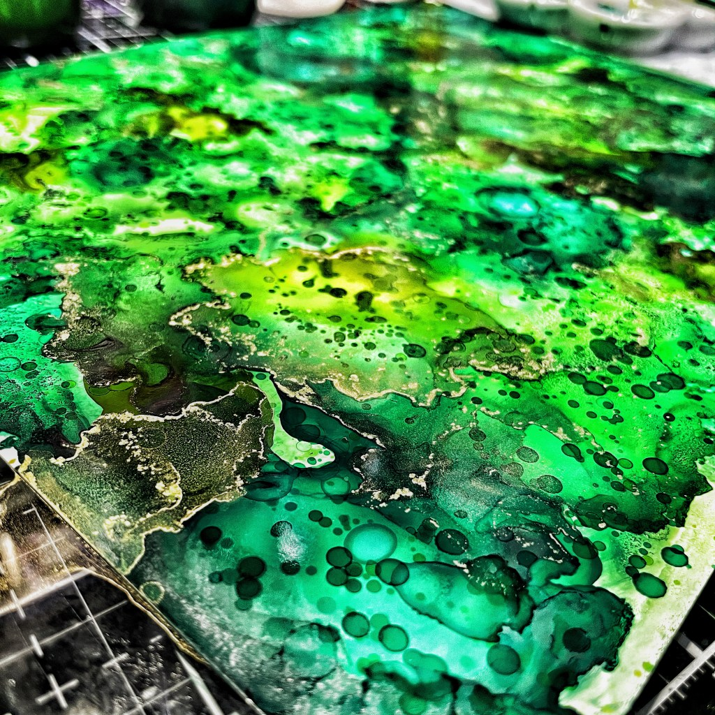 Closeup of alcohol ink splatters on photo paper background.