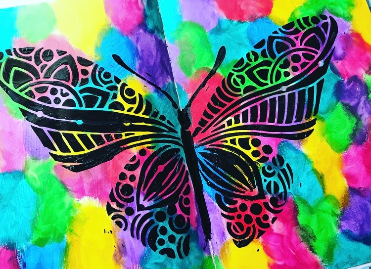 the stencil lifted off leaving behind a beautiful black butterfly on a rainbow background