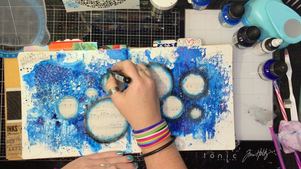 blending Marabu art crayons over the edges of the sheet music circles
