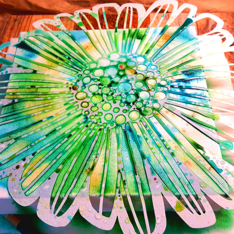 Image showing the TCW929 Felicia Daisy stencil laying on top of the canvas. ColorSparx powders have been sprinkled randomly and activated with water.