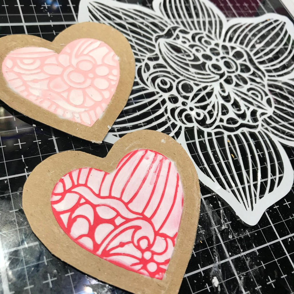TCW9004 Light and Fluffy Modeling Paste through TCW930 Cupped Daffodil 6x6 Stencil with a palette knife onto heart shaped paper cookies