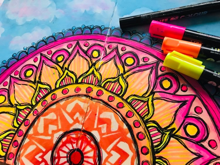 adding details to the sunrise using paint pens in fluro and black