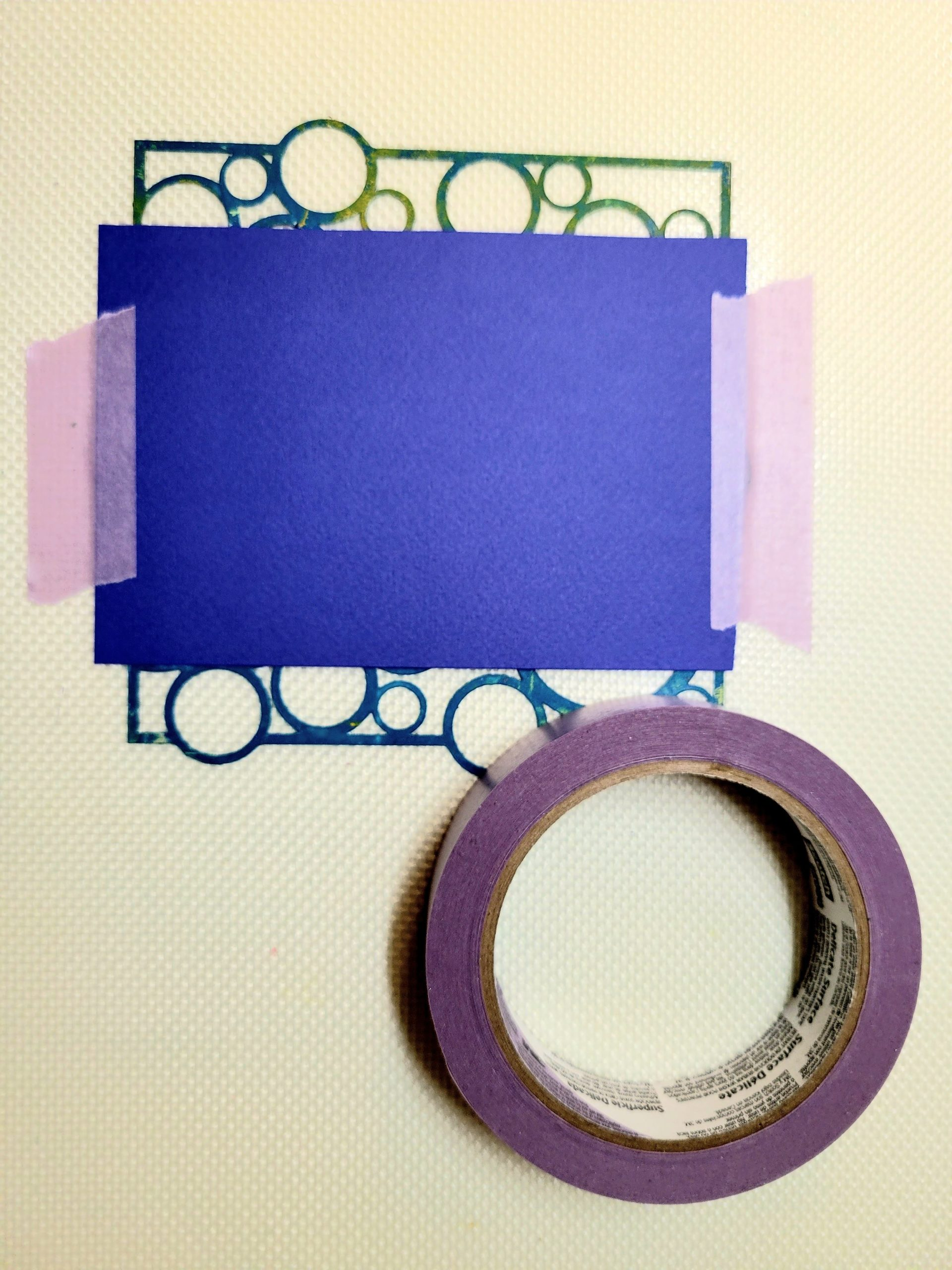 Image showing the paper taped down over the stencil using 3M Delicate Surface tape.