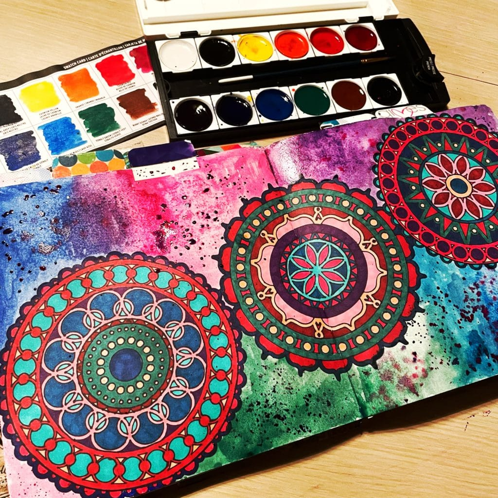 watercolor background around the stenciled mandalas