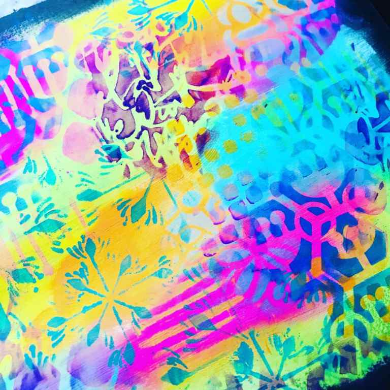 close up of rainbow colored background with lots of stencil work