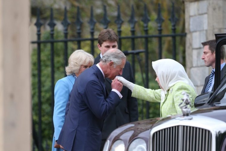 Prince Charles kisses The Queen's hand as she arrives for the beacon lighting. I-images