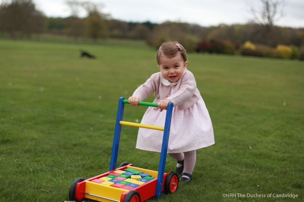 Princess Charlotte totters with her toys in the garden.