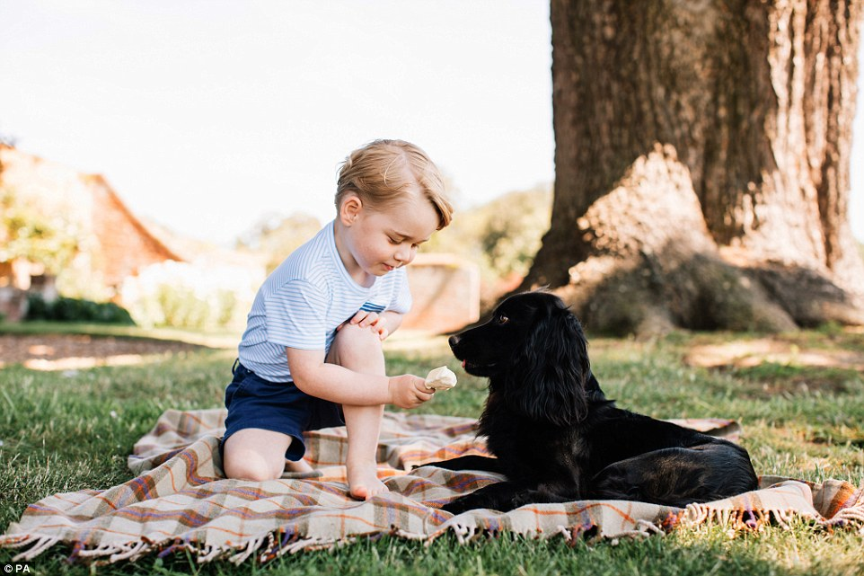 Prince George with Lupo, offering him ice-cream. Matt/PA