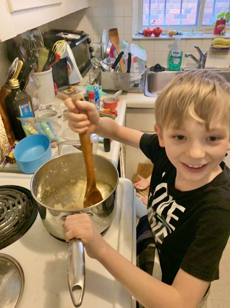 young child delighted as he mixes baking ingredients