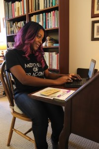 author smiling while writing at a desk