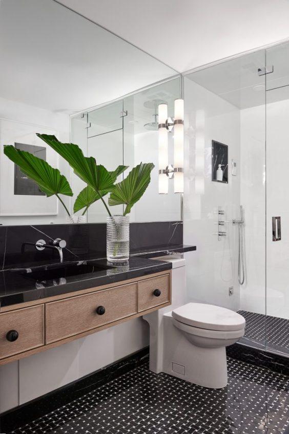 Gorgeous modern bathroom design with light wood vanity, black countertops and black and white patterned floor tile - the design co. #bath #bathroomremodel #bathroomideas #bathroomdecor