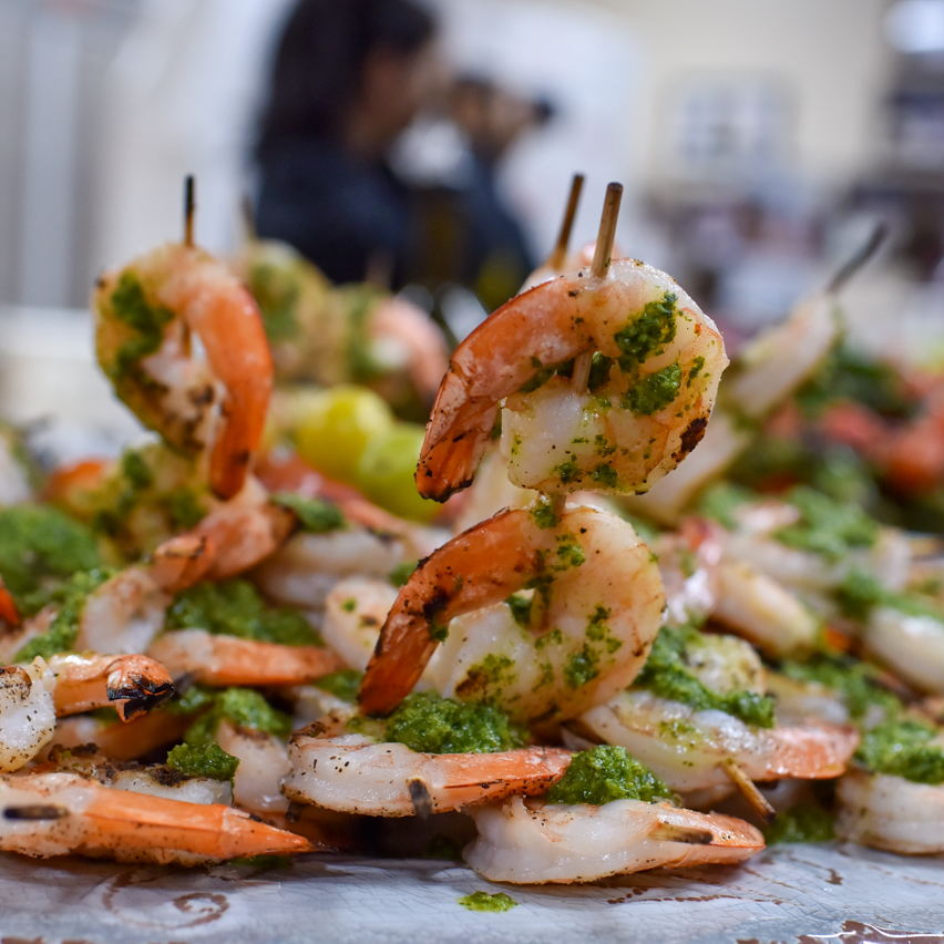 Skewered and grilled shrimp with chimichurri sauce.