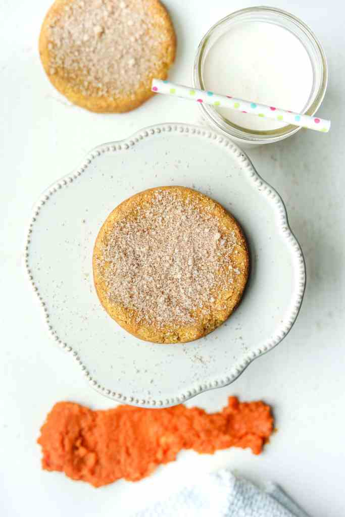 A low carb pumpkin spice cookie sitting on a serving plate surrounded by a glass of milk and another cookie.