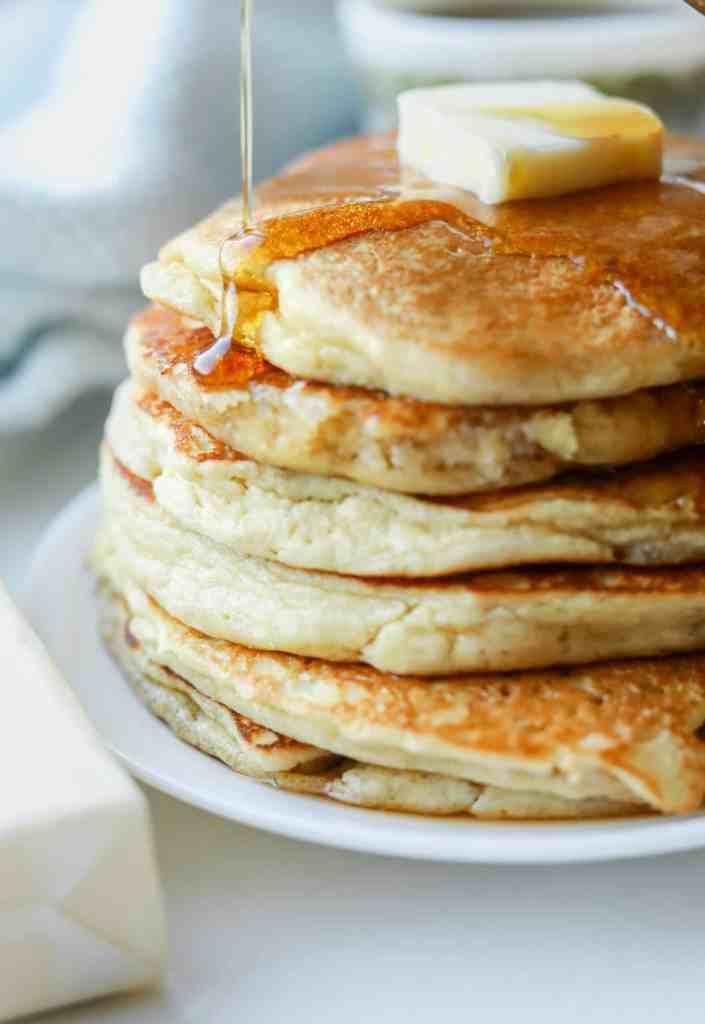 A stack of pancakes with syrup running down the left side of them.