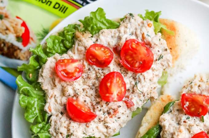 Open faced keto salmon sandwiches laying on a plate, and topped with cherry tomatoes.