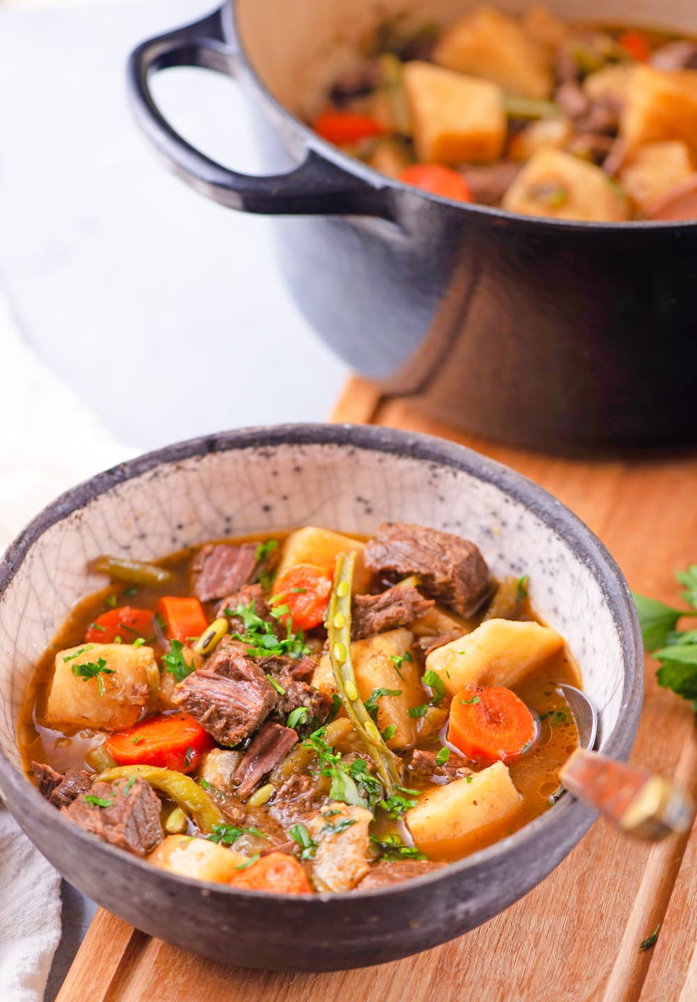 Keto beef stew in a bowl next to an entire pot of it.