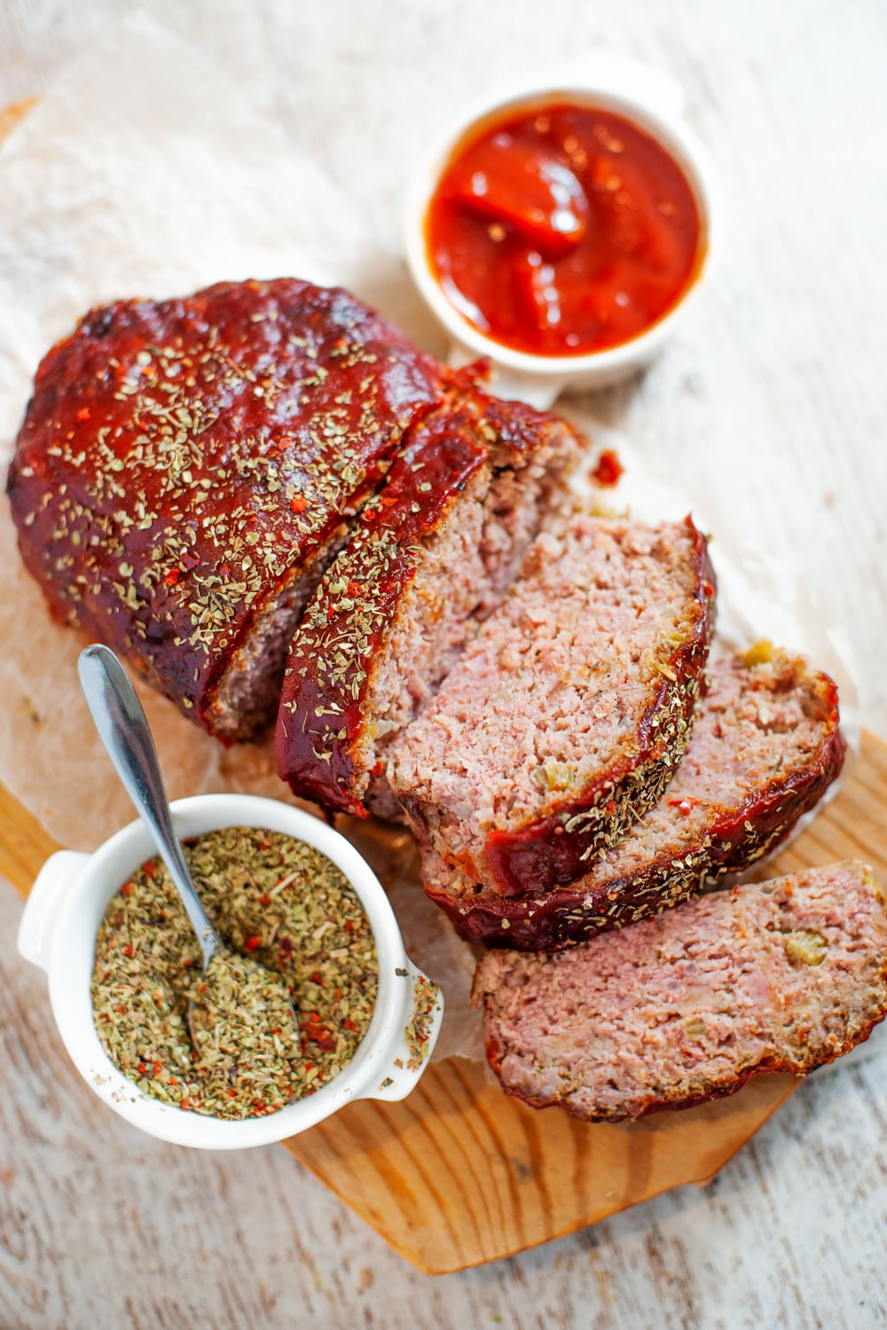 Sliced meatloaf on a cutting board with spices and ketchup next to it.