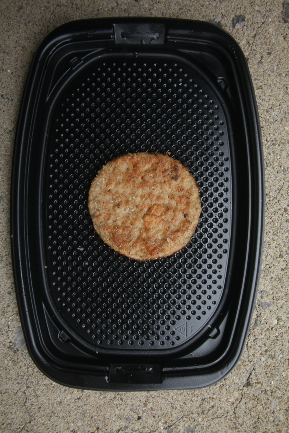 A breakfast sausage patty on a black take-out container.