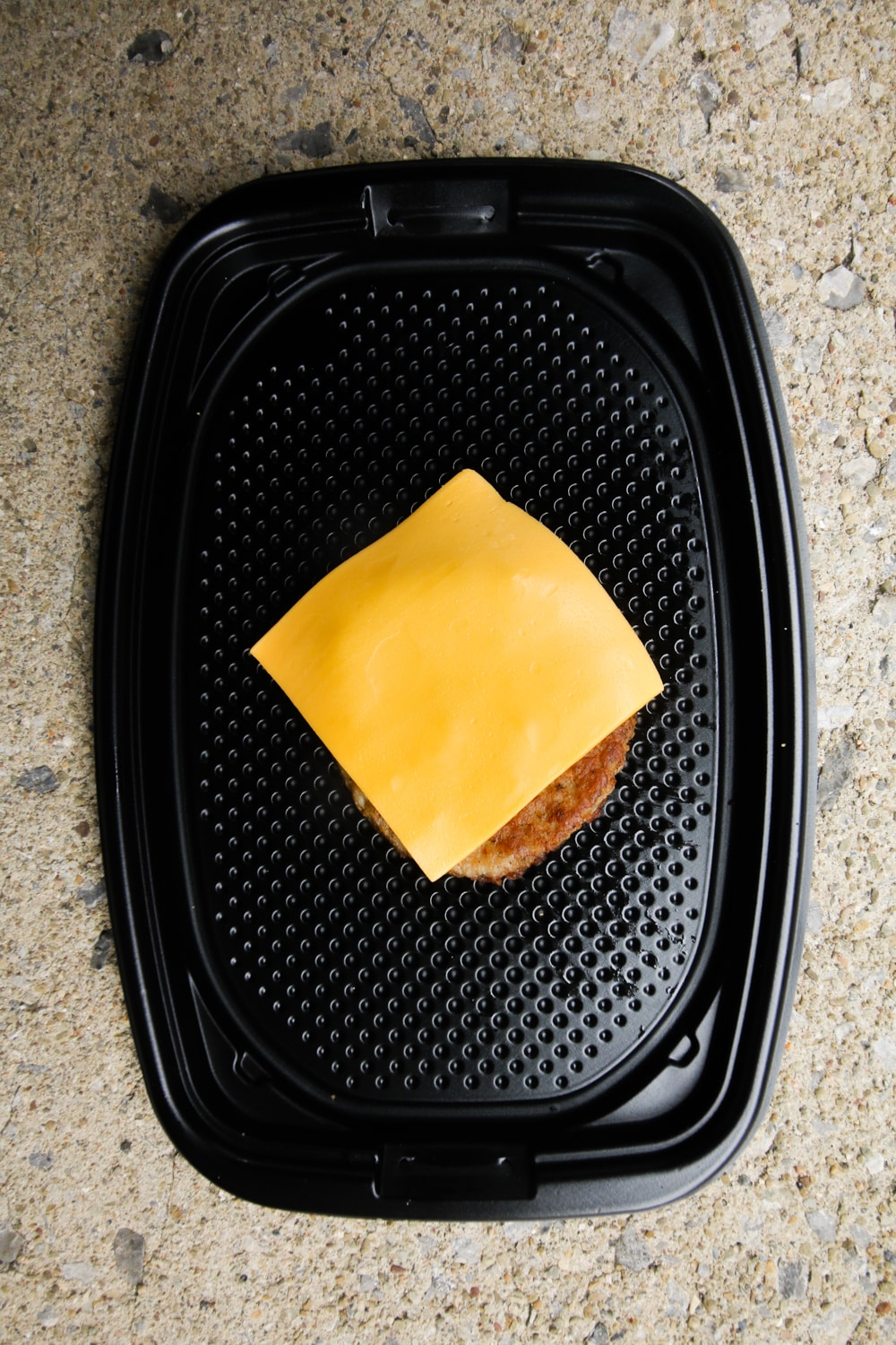 A piece of sausage topped with cheese on a black take-out container.