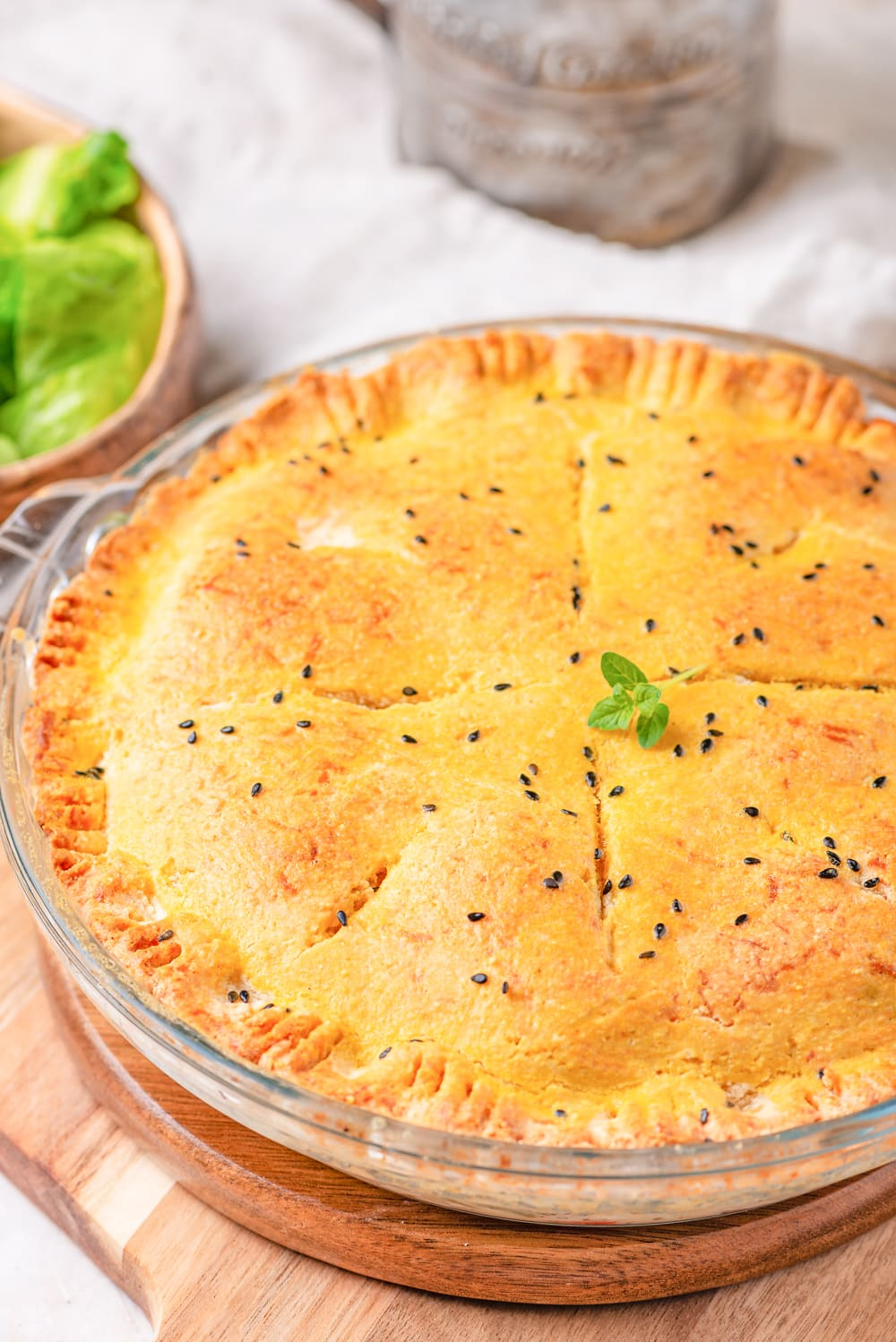 Chicken pot pie in a pie plate and topped with micro-greens.
