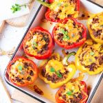 Bell peppers on baking sheet, cut in half, and filled with ground beef & cheddar cheese.