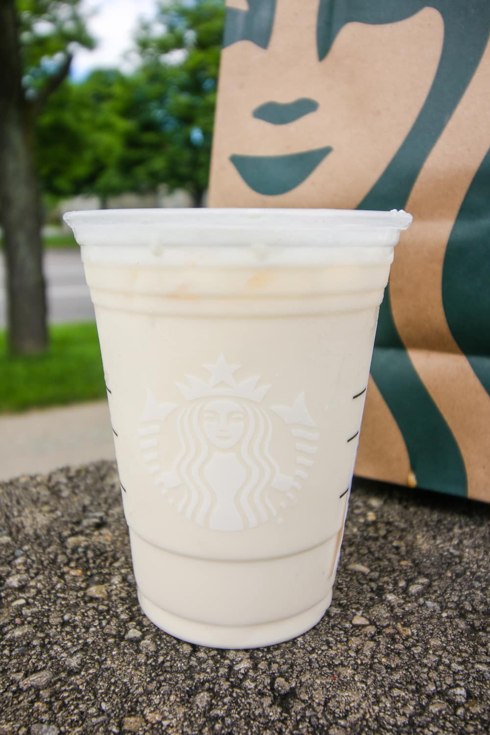 A white tea drink mixed with cream and sweetener in a cup.