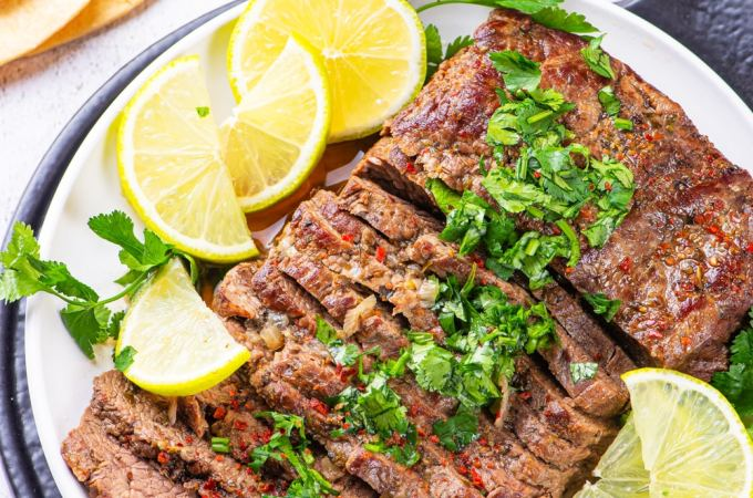 Flank steak cut up on a white plate covered in chimichurri and surrounded by lemons.