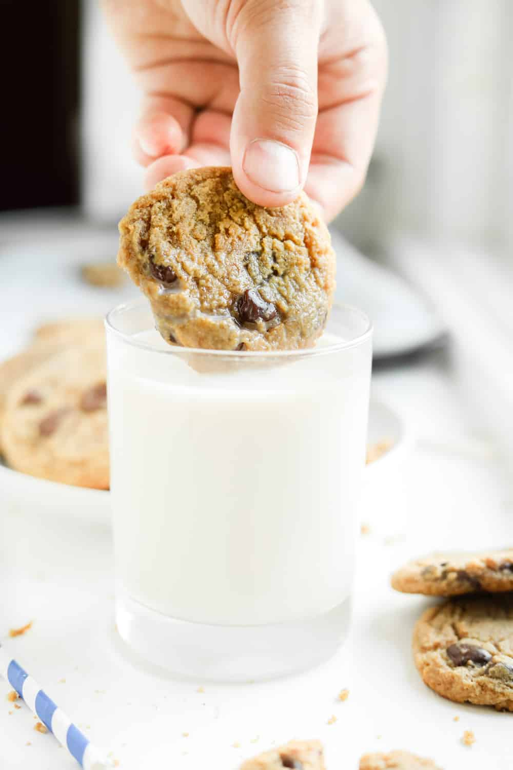 A glass of milk with a chocolate chip cookie about to be dipped in it.