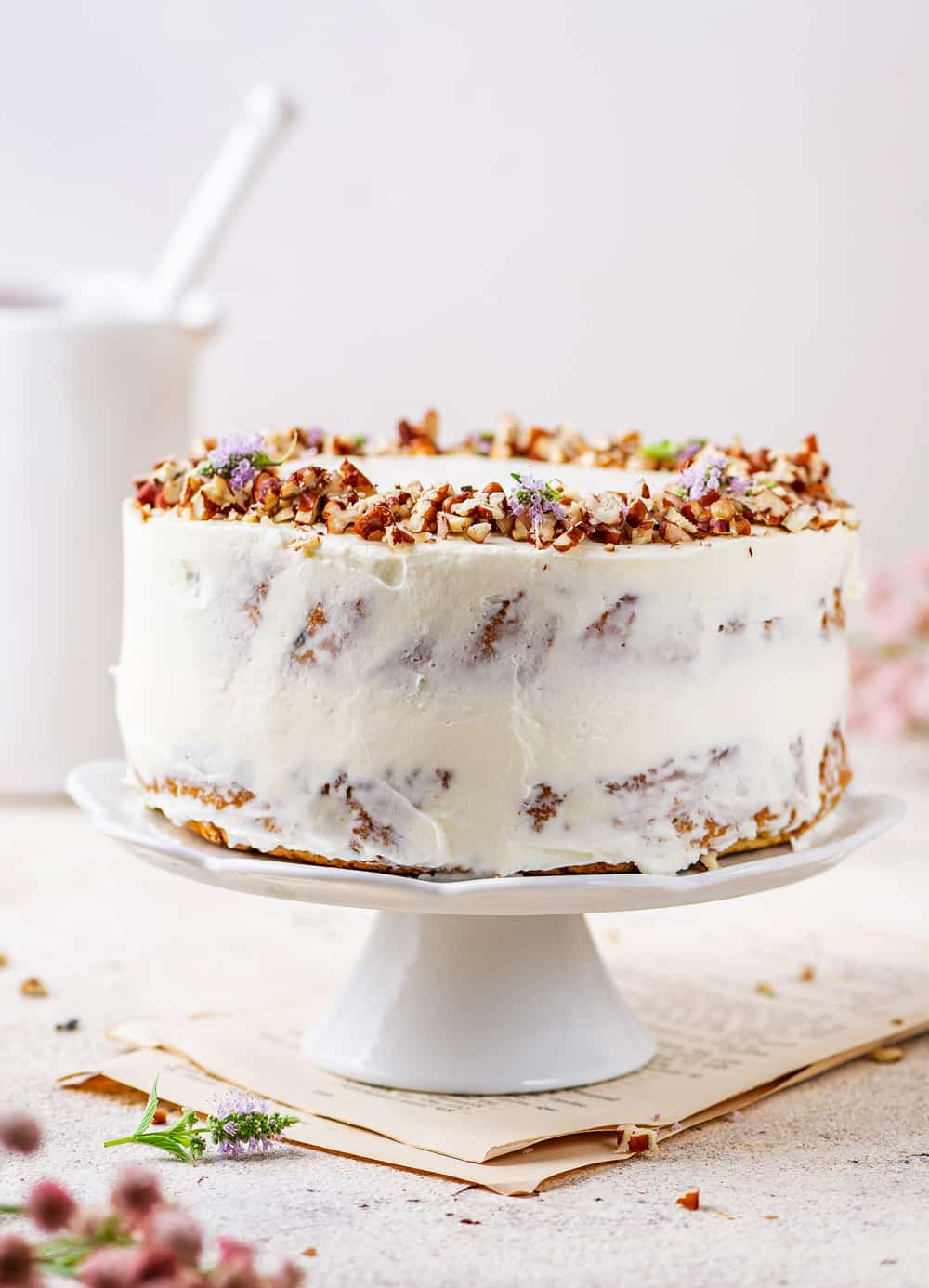 Carrot Cake topped with pecans on a white serving tray.