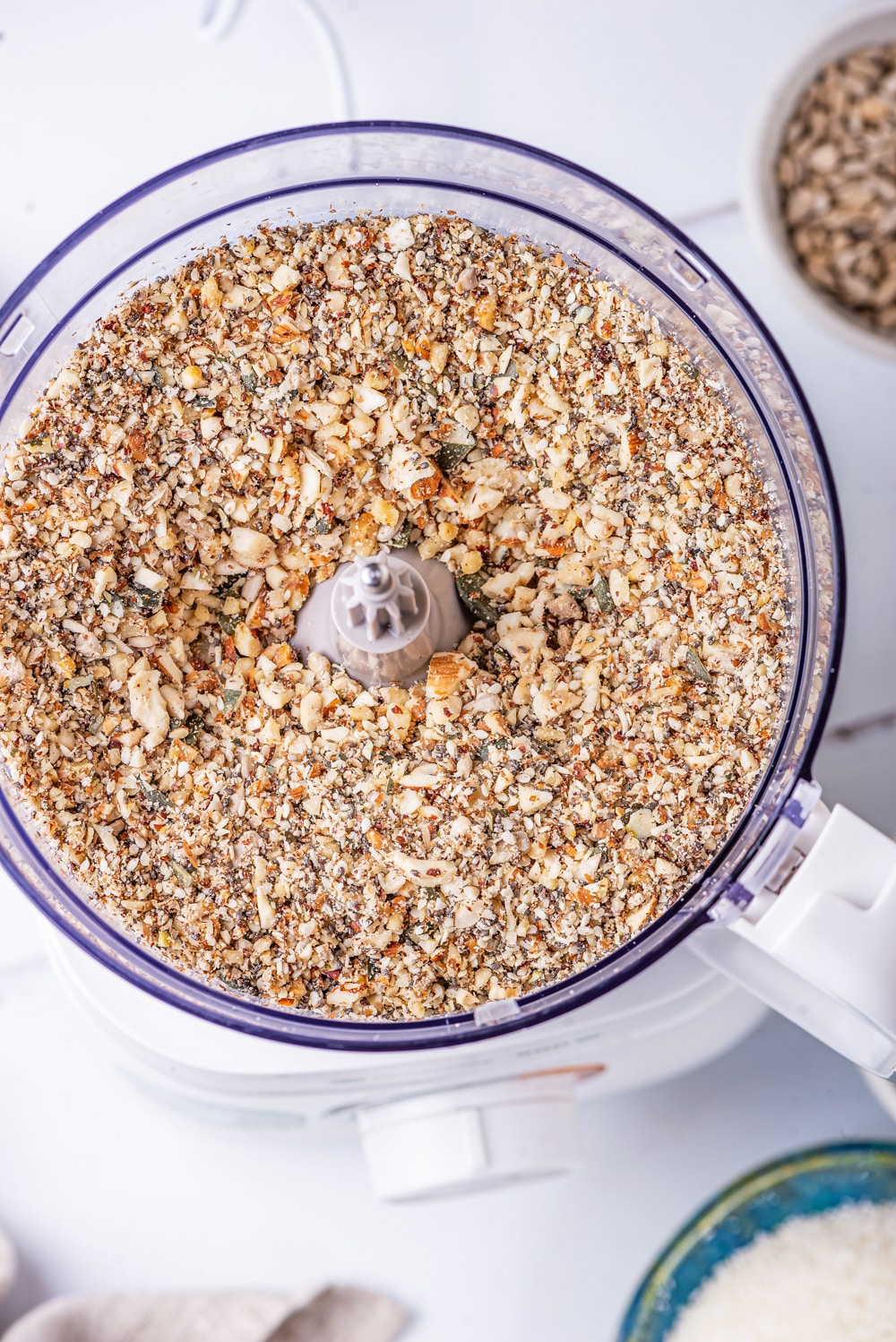 A food processor filled with crushed up nuts and seeds on a white table.