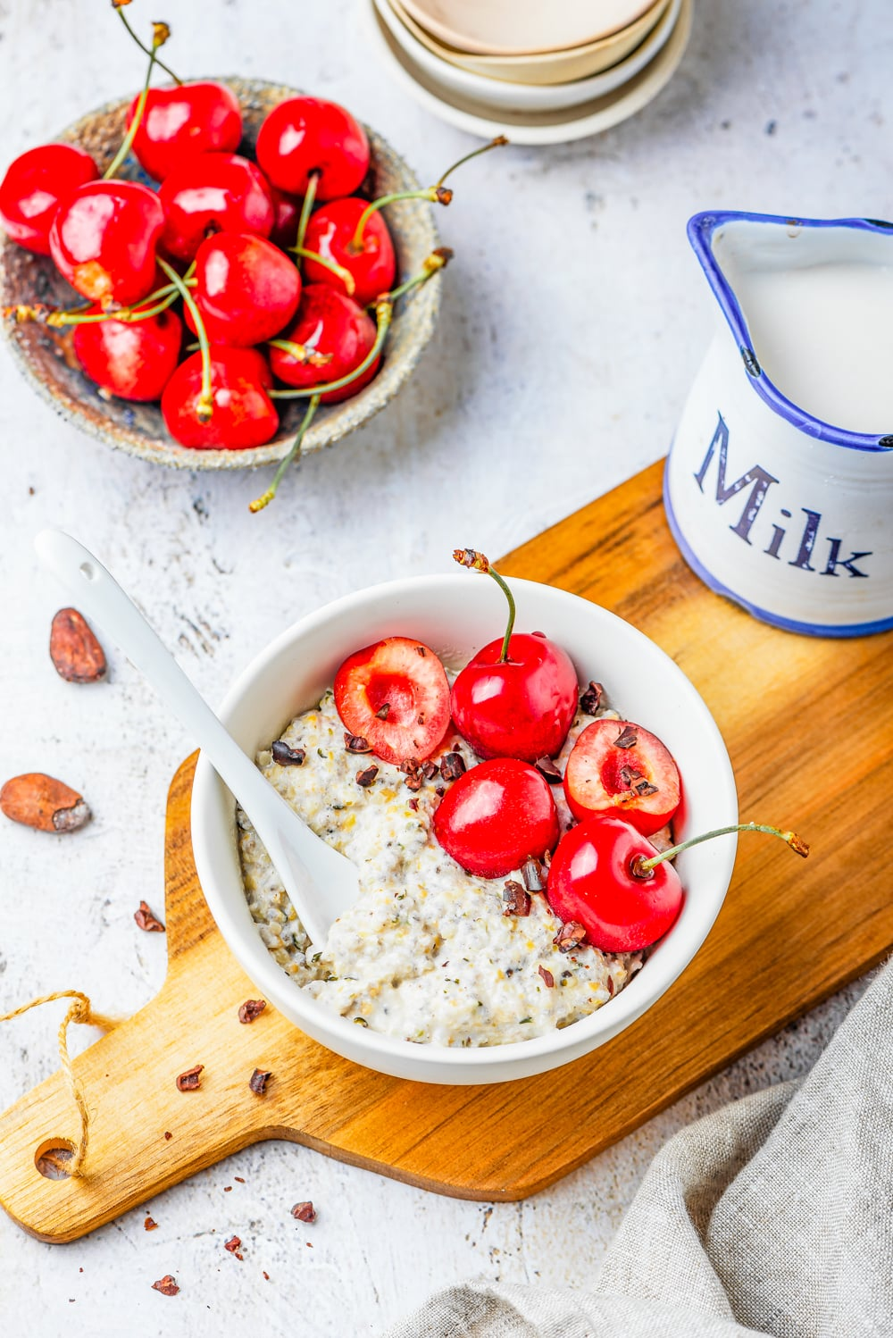 A bowl full of oatmeal, bits of dark chocolate, and cherries on a wooden cutting board.